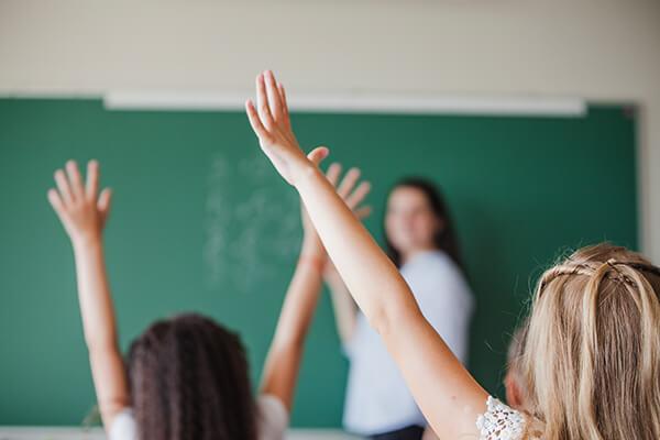 Crianças levantando a mão em sala de aula