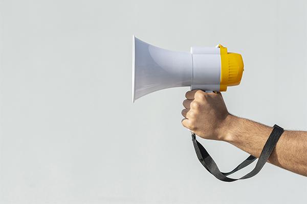 Mão de ativista segurando megafone