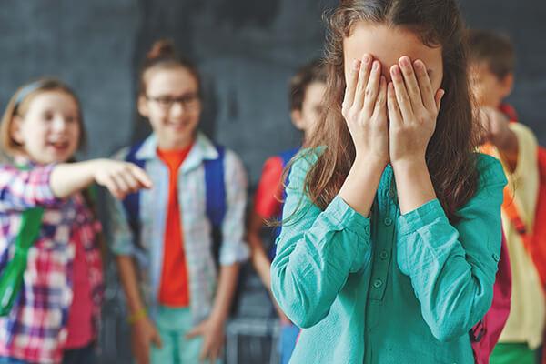 Crianças praticando bullying com menina que gagueja