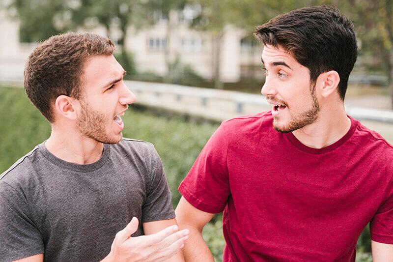 Dois rapazes conversando animadamente.