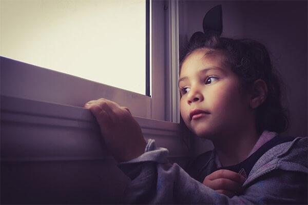 Menina pensativa olhando pela janela