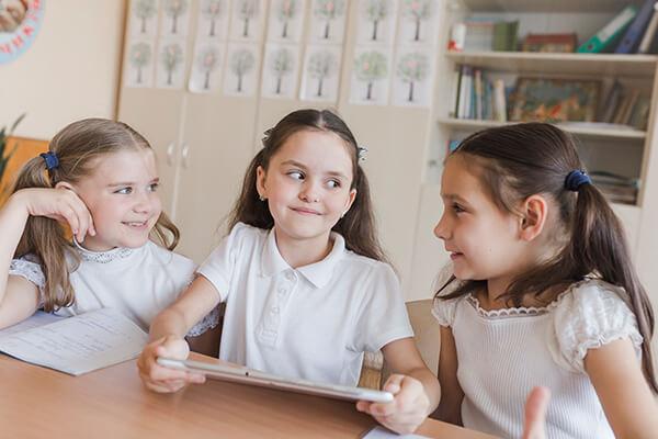 três meninas conversando na mesa