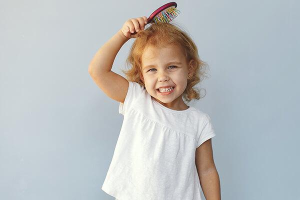 Criança escovando seu próprio cabelo