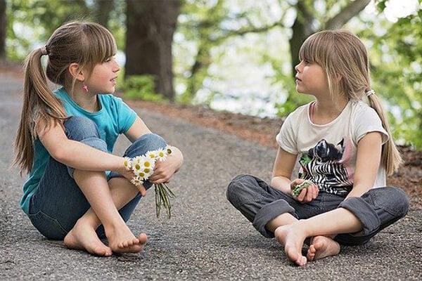 Duas meninas sentadas no chão e conversando