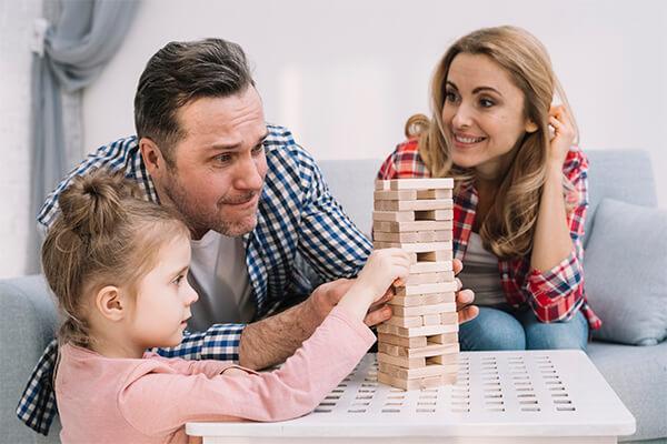 Pais empilhando blocos de madeira com criança