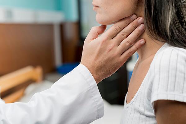 Médico apalpando garganta de paciente