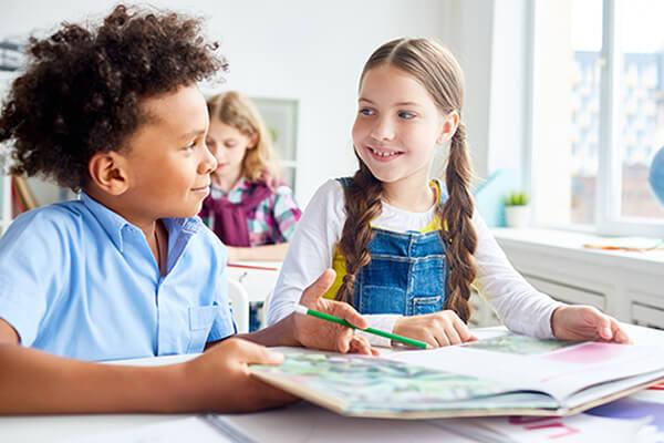 Duas crianças conversando em sala de aula