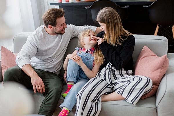 Pais sentados com criança no sofá