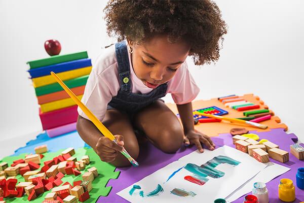 Criança desenhando com pincel no chão