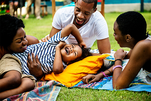 Família brincando com criança rindo na grama
