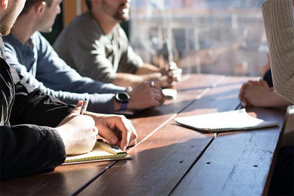 Pessoas sentadas à mesa escrevendo