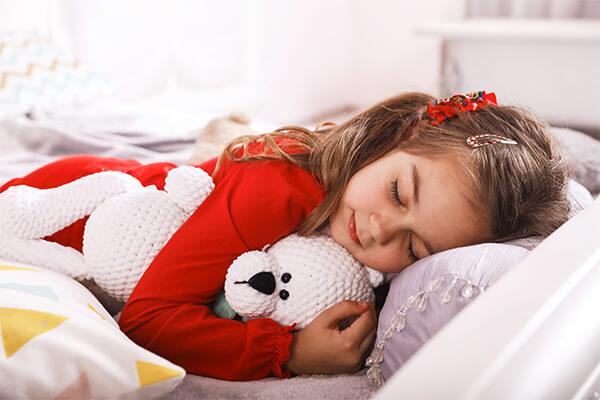 Criança dormindo com bicho de pelúcia
